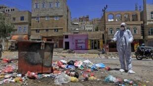 Volontaire désinfectant des ordures à Sanaa, le 30 mars 2020.