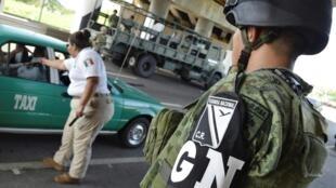 A Tapachula, le 18 juin, une agente de l'agence mexicaine des migrations effectue un contrôle sous le regard d'un soldat de la Garde nationale.