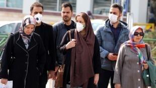 Des Iraniens se protégeant du coronavirus en portant un masque dans les rues de Téhéran le 22 février 2020.