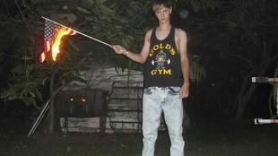Em imagens publicadas no site lastrhodesian.com, o autor do massacre de Charleston, Dylann Roof, de 21 anos, aparece queimando a bandeira dos Estados Unidos.