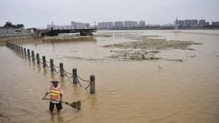 A worker stands on a flooded road (on the left of guardrails) near Minjiang River in Fuzhou, Fujian province