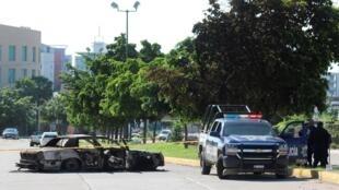 Une voiture de police près d'une carcasse calcinée de voiture à Culiacacn (Mexique) au lendemain d'une bataille rangée entre hommes armés et forces de sécurité, le 18 octobre 2019.
