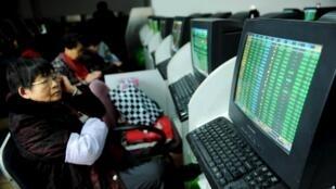 Các nhà đầu tư theo dõi màn hình thông tin chứng khoán tại một nhà môi giới ở Thanh Đảo, tỉnh Sơn Đông, Trung Quốc, ngày 11/01/2016.
