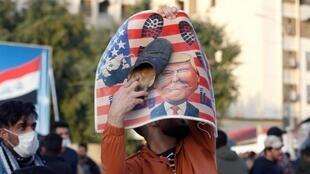 A protester outside the US embassy in Baghdad during a rally to condemn US air strikes on paramilitary bases, Iraq, 1 January 2020.