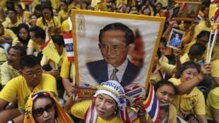 Demonstrators carry a portrait of Thai King Bhumibol Adulyadej.