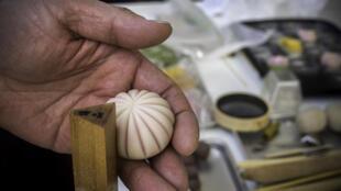 Un pâtissier utilise un manche en bambou pour sculpter les formes de son wagashi.