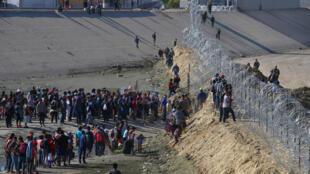 Des migrants se rassemblent derrière le grillage de la frontière qui sépare le Mexique des États-Unis à Tijuana, le 25 novembre 2018.