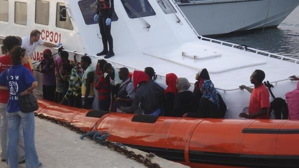 Tunisian migrants rescued from their sunk boat arrive in a coast guard vessel at Lampedusa harbour in Sicily 7 September, 2012