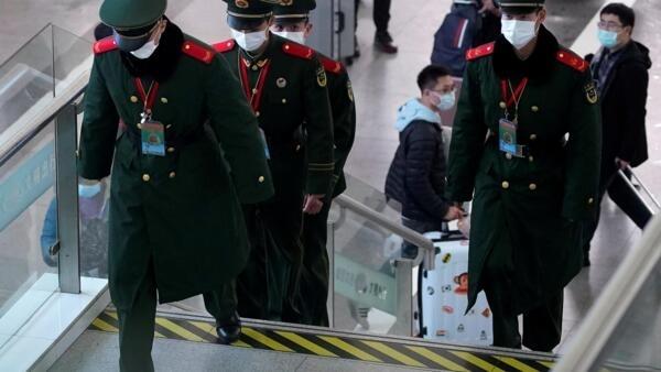 Un groupe de policiers équipé de masques médicaux circule dans la gare de Shanghai, le 22 janvier 2020.