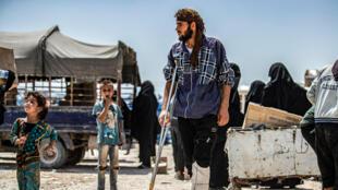 Un homme avec une béquille marche au camp d'al-Hol, dans le nord-est de la Syrie, le 22 juillet 2019, alors que d'autres personnes collectent des colis d'aide humanitaire fournis par l'ONU.