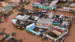 Residents stand on rooftops in a flooded area of Buzi, central Mozambique, 20 March 2019.
