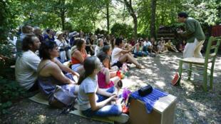 Au Festival du Nombril du Monde, les contes se racontent les pieds dans l'herbe. Ici, Marien Guillé, conteur invité.