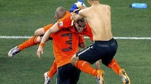 Netherlands' Wesley Sneijder is lifted by teammate John Heitinga as they celebrate in Port Elizabeth