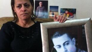 Idn Musallam, a mãe de Muhammad Said Ismail Musallam, mostra uma foto do filho executado por um menino do grupo Estado Islâmico.
