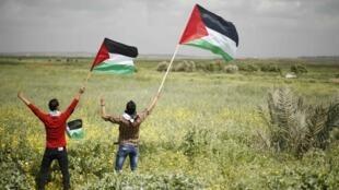Des Palestiniens agitent leur drapeau en direction de la frontière israélienne avec la Bande de Gaza, le 30 mars 2014.
