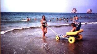 Cadeirante entra no mar com aparelho especial.