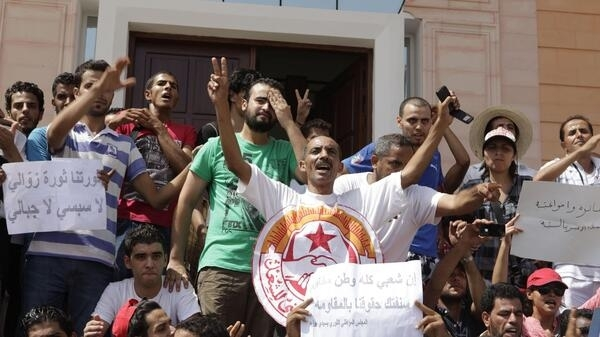 Protesters shout slogans calling for the release of other protesters, who were arrested after clashes with police late last week, outside a court in Sidi Bouzid