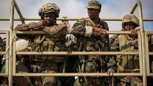 Ugandan soldiers serving the Amisom sit in the back of a military truck in the town of Afgoi