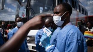 Un membre du Centre biomédical rwandais scanne des passagers dans une station de bus, le 22 mars 2020 à Kigali.