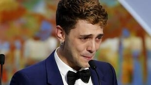 Xavier Dolan is overcome with emotion on receiving the Cannes Jury Prize along with Jean-Luc Godard