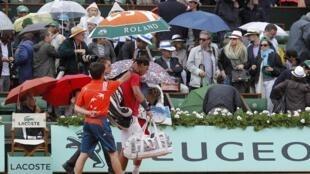 O tenista espanhol Rafael Nadal deixa a quadra depois de a final  de Roland Garros ser suspensa por causa da chuva.