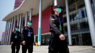 Des agents de sécurité patrouillent devant le centre de convention de Wuhan transformé en hôpital pendant la crise sanitaire le 9 avril 2020 (image d'illustration).