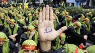 """Um manifestante mostra a palma da mão, onde se lê """"Nós respondemos ao teu apelo"""""""