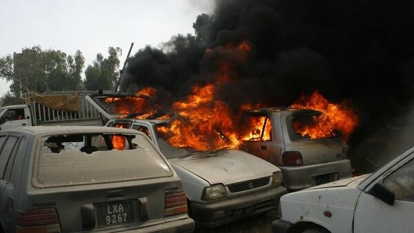 An angry mob set cars alight inside a police compound during clashes in Faisalabad, Pakistan