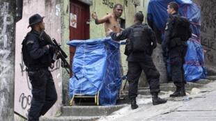 """Policiais revistam suspeito durante operação """"Choque da Paz"""" na Rocinha."""