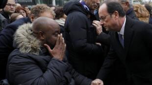 O presidente François Hollande cumprimenta uma vítima dos atentados de 13 de novembro de 2015 nos arredores do Stade de France.