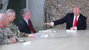 Rais wa Marekani Donald Trump na Mshauri wa masuala ya usalama wa taifa wa Marekani John Bolton, wakikutana na maafisa kijeshi kabla ya kuzuru kambi ya kijeshi ya Al Asad, Iraq Desemba 26, 2018.