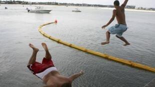 Two boys jump off a bridge near oil containment boom into Wolf Bay, Florida