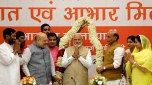 លោកណារិន្ទ្រ ម៉ូឌី អមដោយកម្រមាលា ប្រៀបបាននឹងព្រះមួយអង្គនៃសាសនាហិណ្ឌូ។ ក្រុងញូដេលី ទីស្នាក់ការបក្ស BJP ថ្ងៃទី២១ ឧសភា ២០១៩