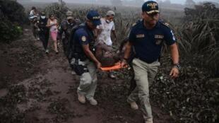 Polisi wakimuokoa mtu aliyejeruhiwa wakati wa mlipuko wa volkano ya Fuego, katika kijiji cha El Rodeo, kilomita 35 kusini mwa mji mkuu wa Guatemala, tarehe 3 Juni 2018.