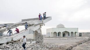 Des enfants jouent dans les décombres d'un bâtiment qui servait de base militaire à Daech, détruit par une frappe aérienne de la coalition. Hammam al-Alil, Irak, décembre 2016.