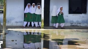 Indian muslim girl students stand outside their classroom as they wait for their teacher in Sonitpur District.