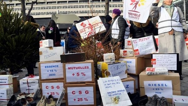 Demonstrators stand in front of boxes reading the increases of the cost of life as part of a call of nine retiree organisations for purchasing power, in front of the French Economy and Finance Ministry in Paris, on December 18, 2018.