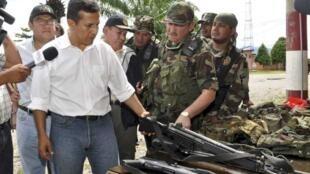 El presidente peruano Ollanta Humala examina las armas decomisadas.