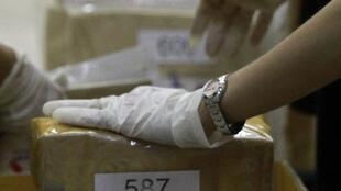 Thai narcotics officials check boxes of confiscated drugs