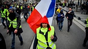 A Yellow Vest protester in Nantes, France, holds a French flag during an anti-government demonstration, January 12, 2019