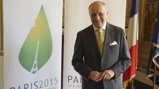 French Foreign Affairs Minister Laurent Fabius poses in front of the Paris 2015 climate change conference logo in his office in Paris, France, May 22, 2015, after an interview with Reuters.