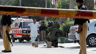 Des démineurs vérifient le contenu d'un sac peu de temps après l'attaque du consulat de Chine à Karachi.