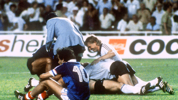 Michel Platini's disappointment... The French midfielder sits on the pitch while West German players celebrate after Horst Hrubesch won the penalty kick in extra time, leading West Germany to World Cup final, Seville, 8 July 1982.