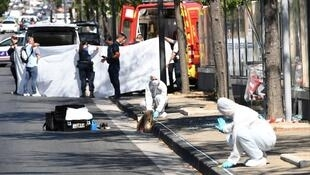 A white sheet is erected as a body of a victim is evacuated to a waiting ambulance while French forensic police officer search the site following a car crash on August 21, 2017.