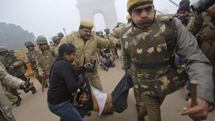 Police detain a demonstrator in front of the India Gate during a protest in New Delhi , 23 December