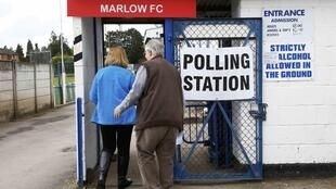 Voters arrive to cast their ballots at a polling station set up at the local football club in Marlow, central Britain, 7 May 2015.