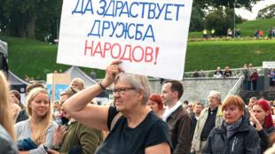 Une femme brandit une pancarte où il est écrit «vive l'amitié entre les peuples», lors d'un rassemblement citoyen à Tallin en Estonie, le 6 septembre 2015.