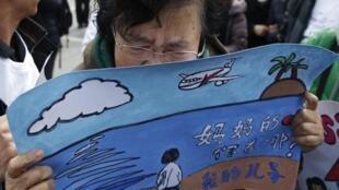 一位MH370失聯飛機乘客家屬在北京雍和宮前表達對兒子的思念。2015-03-08