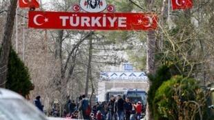Un groupe de migrants attend dans le no man's land entre la Turquie et la Grèce, au poste frontière turc de Pazarkule avec la ville grecque de Kastanies, au nord du fleuve Evros, le 28 février 2020.