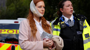 An injured woman is led away after an incident at Parsons Green underground station in London, Britain, September 15, 2017.